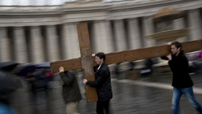 Pilgrims carry a large cross through St. Peter's Square while cardinals meet in conclave in the Sistine Chapel to elect a new pope at the Vatican, Wednesday, March 13, 2013. Cardinals remained divided over who should be pope on Wednesday after three rounds of voting, an indication that disagreements remain about the direction of the Catholic Church following the upheaval unleashed by Pope Benedict XVI's surprise resignation. (AP Photo/Emilio Morenatti)