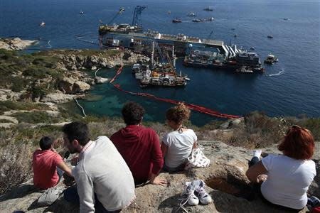 People look on as the capsized cruise liner Costa Concordia lies on its side next to Giglio Island