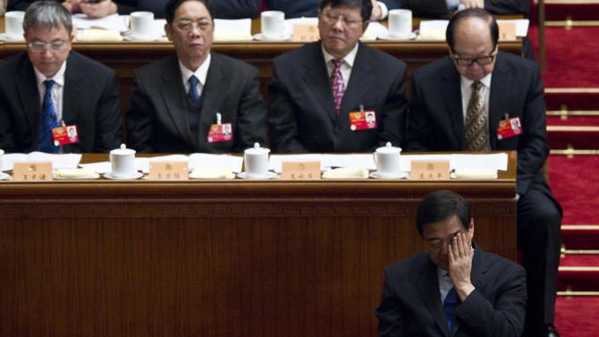 In this March 13, 2012 photo, Chongqing Municipality Communist Party secretary Bo Xilai, front, reacts during the closing session of the Chinese People's Political Consultative Conference held at Beijing's Great Hall of the People. China said Tuesday April 1, 2012,  the ousted high-profile leader Bo Xilai, once a contender for a seat in the top leadership, has been suspended from key Communist Party positions in the latest development in the country's biggest political crisis in years. (AP Photo/Alexander F. Yuan)