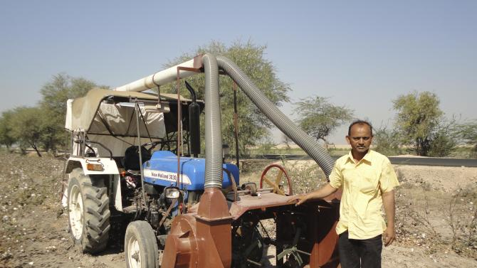 In this undated photo provided by the National Innovation Foundation, Nattubhai Vader stands next to a machine called Cotton Harvester, which he invented in India. Vader, a farmer from the state of Gujarat, invented the apparatus that fits over a tractor after watching women and children performing the slow grueling work of harvesting an especially troublesome variety of cotton. (AP Photo/National Innovation Foundation)