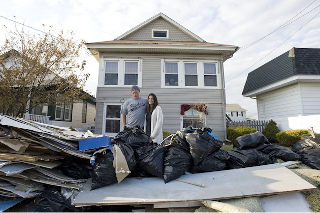 Jared and Sarah Lenko stand in front of their Ocean City, N.J. house on Saturday, Nov. 10 2012 that was under two feet of water during Superstorm Sandy. (AP Photo/The Press of Atlantic City, Matthew S
