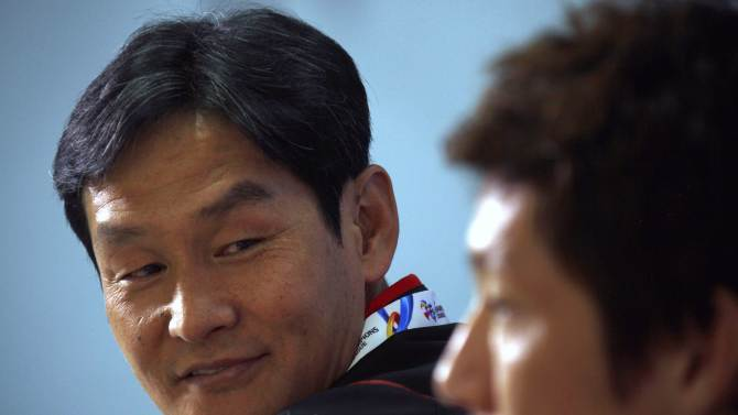 Choi, coach of FC Seoul soccer team, looks across at team captain Kim during a media conference at Parramatta Stadium