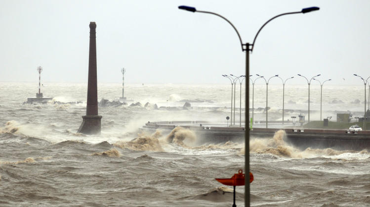 High waves crash against the sea wall during a heavy wind storm in Montevideo, Uruguay, Wednesday, Sept. 19, 2012. A powerful storm blew across the southern cone of South America, breaking windows in several buildings in Uruguay's capital, toppling about a hundred trees and cutting off three highways due to flooding. (AP Photo/Matilde Campodonico)
