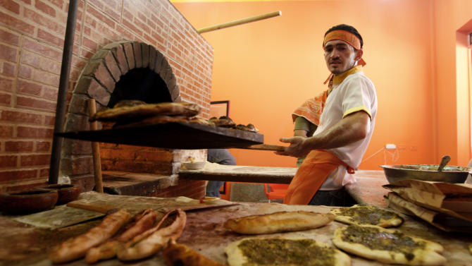 """In this Tuesday, June 11, 2013 photo, an employee works at """"Damashki"""" or """"The Guy From Damascus"""" bakery co-owned by Bassel Shunar, a Palestinian by origin who was born in Syria but who fled the country and arrived in the Gaza Strip two months ago. The civil war in Syria is increasingly hurting Hamas-ruled Gaza financially, according to several officials in the Islamic militant group and in Islamic charities. (AP Photo/Hatem Moussa)"""
