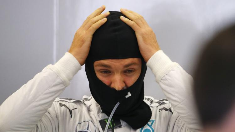 Mercedes Formula One driver Rosberg adjusts his hood during a practice session at the Belgian F1 Grand Prix in Spa-Francorchamps