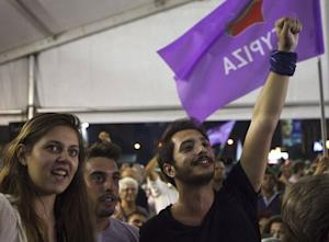 Supporters of leftist Syriza party react at the party's…