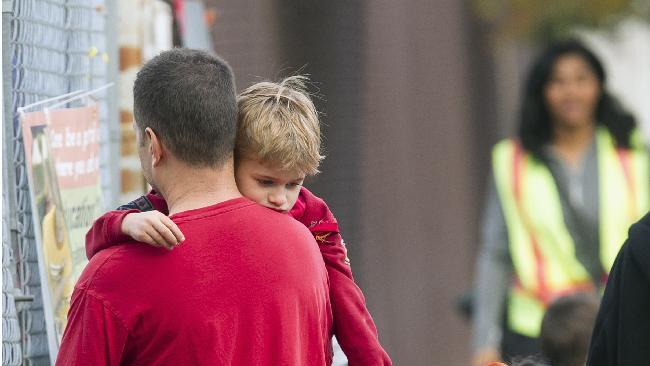 Tom Fico holds his son Lucas, 5, as they drop off his older brother Jake, not seen, at the Theodore Roosevelt School in Burbank, Calif., early Monday, Dec. 17, 2012. Teachers, parents and students are making an anxious return to school this week after a gunman stormed into Sandy Hook Elementary School in Newtown, Conn., on Friday, shooting to death 26 people before killing himself. (AP Photo/Damian Dovarganes)