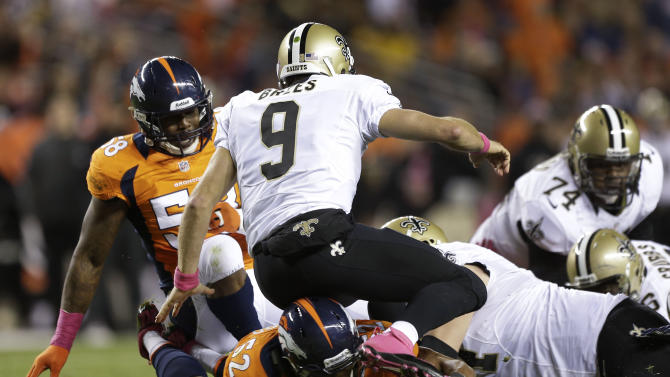 New Orleans Saints quarterback Drew Brees (9) fumbles the ball as he is hit by Denver Broncos outside linebacker Wesley Woodyard (52) in the second quarter of an NFL football game, Sunday, Oct. 28, 2012, in Denver. (AP Photo/Jack Dempsey)