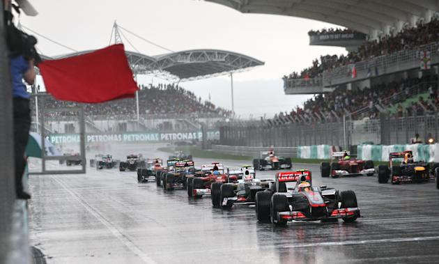 Formula One race cars line up during Formula One's Malaysian Grand Prix at the Sepang International Circuit in Sepang on March 25, 2012  AFP PHOTO / POOL / DITA ALANGKARA (Photo credit should read