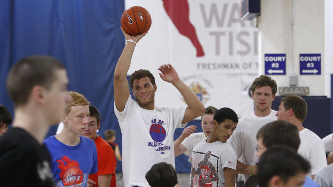 Los Angeles Clippers' Blake Griffin, center, holds the basketball high as campers move to new stations at his basketball camp in Oklahoma City, Tuesday, Aug. 2, 2011. (AP Photo/Sue Ogrocki)
