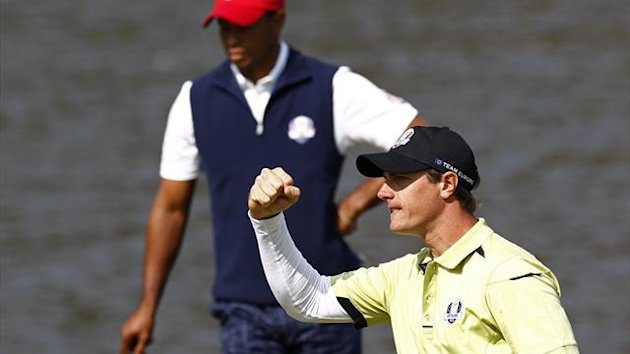 Colsaerts reacts to sinking a birdie putt in front of U.S. golfer Woods