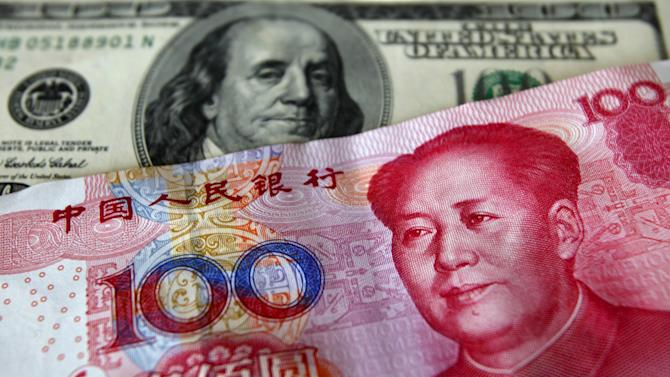File photo of a yuan banknote displayed next to a U.S. dollar banknote for the photographer at a money changer in Taiwan