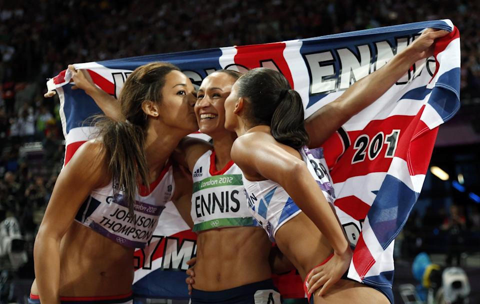Britain's gold medal winner Jessica Ennis is kissed by her teammates Katarina Johnson-Thompson, left, and Louise Hazel after the women's heptathlon during athletics competition in the Olympic Stadium at the 2012 Summer Olympics, Saturday, Aug. 4, 2012, in London. (AP Photo/Matt Dunham)
