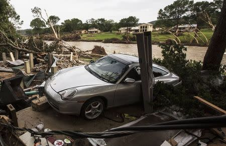 A totaled Porsche rests against the foundation of a home destroyed by the Memorial Day weekend floods in Wimberley Texas