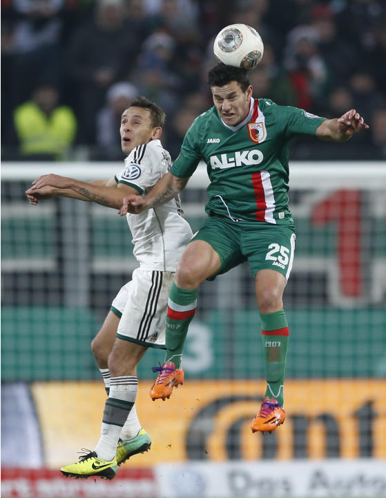 Augsburg's Raul Bobadilla of Argentina, right, and Bayern's Rafinha of Brazil challenge for the ball during the German soccer cup third round match between FC Augsburg and FC Bayern Munich in