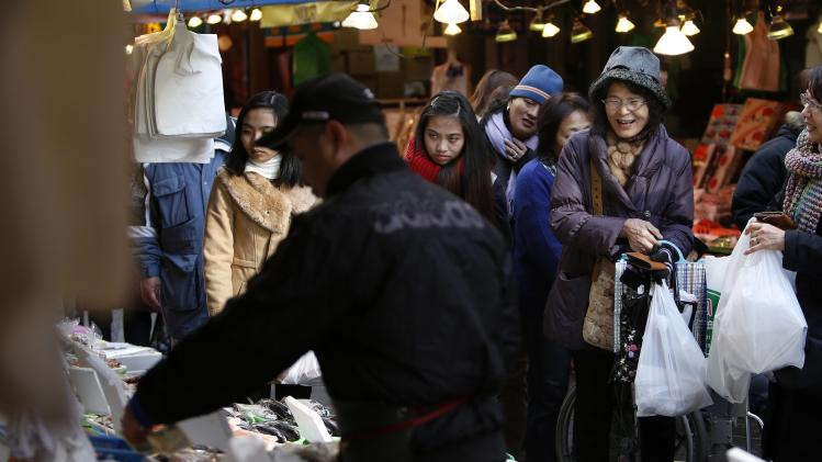 A shopper smiles as she buys seafood at a shopping district in Tokyo