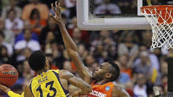 Marquette guard Vander Blue (13) shoots as Syracuse forward Rakeem Christmas (25) defends during the second half of the East Regional final in the NCAA men's college basketball tournament, Saturday, March 30, 2013, in Washington. (AP Photo/Pablo Martinez Monsivais)
