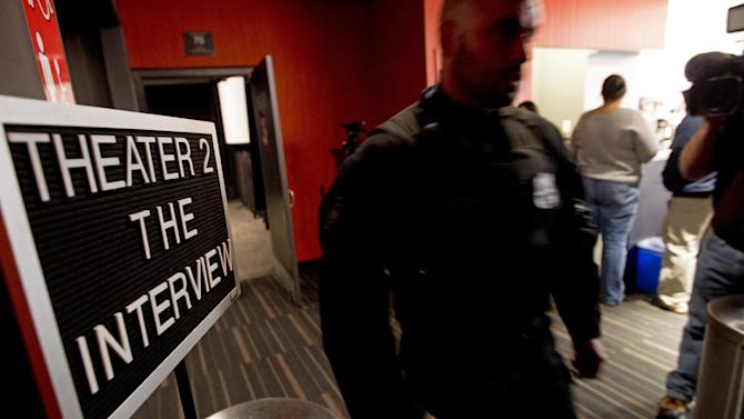 A police officer keeps watch as moviegoers enter the theater to watch The Interview at West End Cinema in Washington, Thursday, Dec. 25, 2014. Hundreds of theaters Thursday, from The Edge 8 in Greenville, Alabama, to Michael Moore's Bijou by the Bay in Traverse City, Michigan, made special holiday arrangements for the Seth Rogen-James Franco comedy depicting the assassination of North Korean leader Kim Jong Un. Sony Pictures had initially called off the release after major theater chains dropped the movie that was to have opened on as many as 3,000 screens.  (AP Photo/Jose Luis Magana)