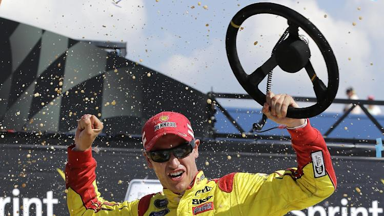 Joey Logano celebrates after winning the NASCAR Sprint Cup series Pure Michigan 400 auto race at Michigan International Speedway in Brooklyn, Mich., Sunday, Aug. 18, 2013. (AP Photo/Paul Sancya)