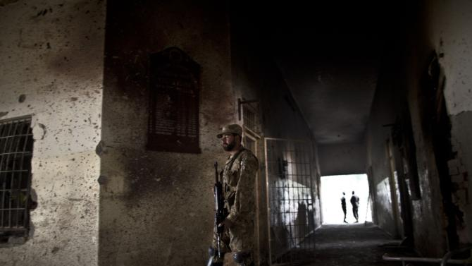 A Pakistani army officer walks between walls riddled with bullet marks inside the Army Public School, attacked Tuesday by Taliban gunmen in Peshawar, Pakistan. (AP Photo/Muhammed Muheisen)