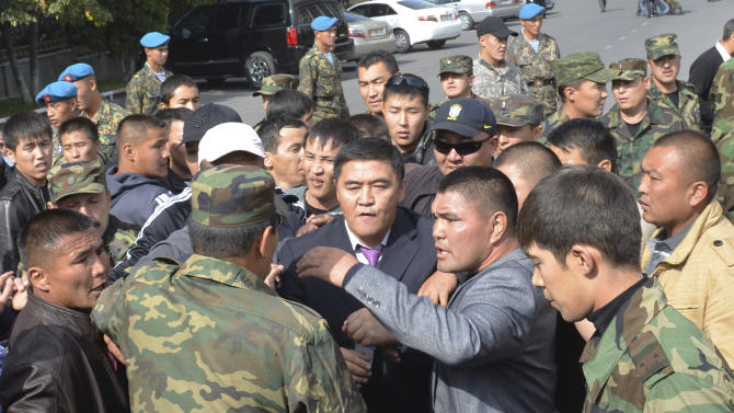 Guards protecting government headquarters, detain Kamchibek Tashiyev, center, surrounded by supporters, after he scaled over a fence surrounding government headquarters in downtown Bishkek, Kyrgyz capital on Wednesday, Oct. 3, 2012. Around 1,000 people gathered in the center of the city for a rally, organized by nationalist politicians Sapar Zhaparov and Kamchibek Tashiyev, ostensibly to demand the nationalization of a controversial gold mine in the east of the Central Asian nation. Police officers protecting the government building, known as the White House, used dogs and smoke bombs to disperse a group of young men who attempted to scale the gates.  (AP Photo/ Abylay Saralayev)