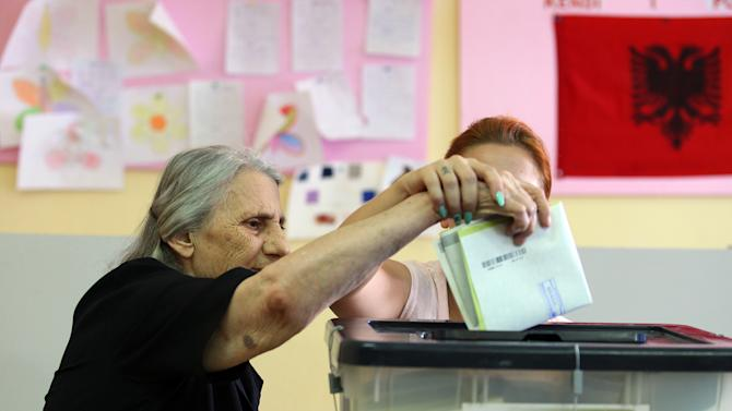 An Albanian woman casts her vote in Tirana, Sunday, June 23, 2013 in the Albanian elections. An Albanian political candidate was shot and a supporter of a rival party killed in an exchange of gunfire near a polling station, police said Sunday, as the country held crucial elections already marred by a dispute that could leave the outcome up in the air. (AP Photo/Hektor Pustina)