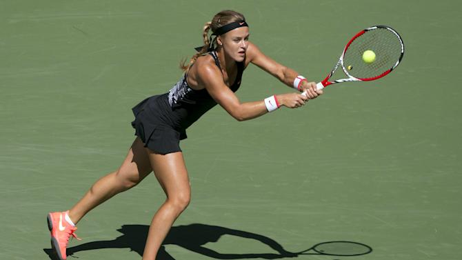 Schmiedlova of Slovakia hits a return to Kvitova of the Czech Republic during their third round match at the U.S. Open Championships tennis tournament in New York