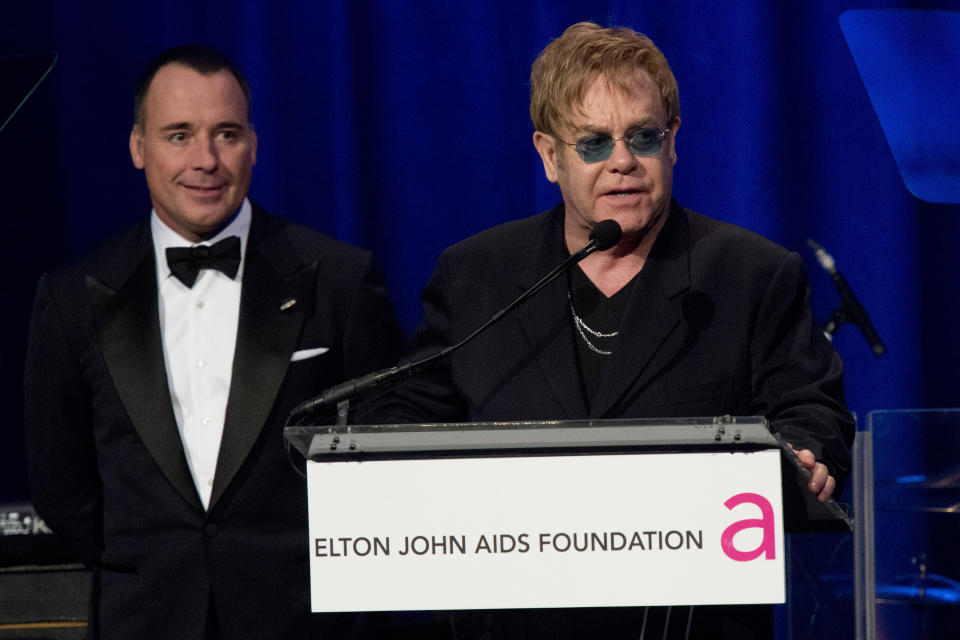 Elton John, right, and David Furnish appear on stage at Elton John's AIDS Foundation's 11th annual Enduring Vision benefit on Monday, Oct. 15, 2012  in New York.  (Photo by Charles Sykes/Invision/AP)