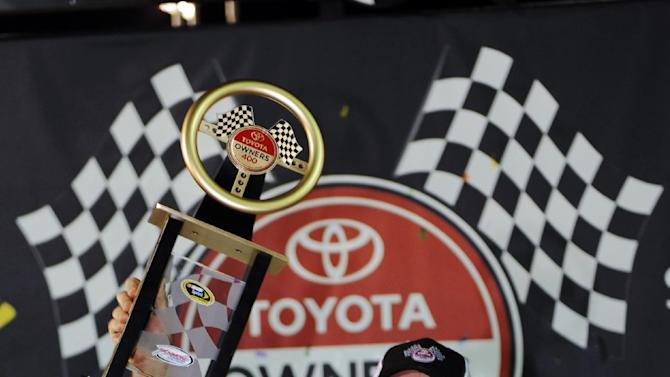 Kevin Harvick holds the trophy as he celebrates winning the Toyota Owner's 400 NASCAR Sprint Cup series auto race at Richmond International Raceway in Richmond, Va., Saturday April 27, 2013.   (AP Photo/Clem Britt)