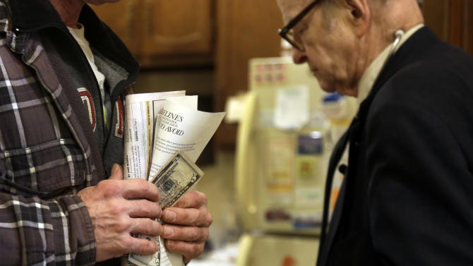 In this Tuesday, Oct. 30, 2012 photo, patient Joe Logsdon holds $5 in his hand to pay for his office visit as Dr. Russell Dohner, right, walks past in Rushville, Ill. When Dohner started practicing medicine in Rushville in 1955, he charged $2, the going rate around town for an office visit but has since raised it to $5. (AP Photo/Jeff Roberson)