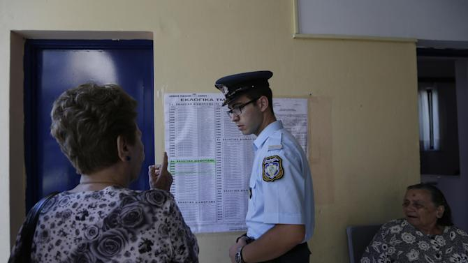 A woman asks a police officer for help at a polling station in Athens, Sunday, July 5, 2015. Greeks began voting early Sunday in a closely-watched, closely-contested referendum, which the government pits as a choice over whether to defy the country's creditors and push for better repayment terms or essentially accept their terms, but which the opposition and many of the creditors paint as a choice between staying in the euro or leaving it. (AP Photo/Petr David Josek)