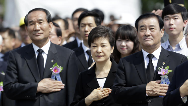 South Korean President Park Geun-hye, center, salutes to a national flag during a 58th Memorial Day ceremony at the National Cemetery in Seoul, South Korea, Thursday, June 6, 2013. (AP Photo/Lee Jin-man, Pool)