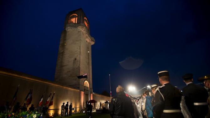 ANZAC Day observers listen to national anthems during a dawn service to mark the 100th anniversary of ANZAC Day in Villers-Bretonneux, in northern France