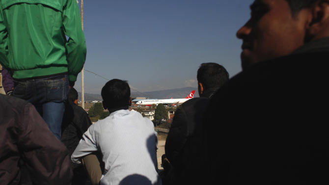 Nepalese watch workers try to remove a Turkish Airlines jet that skidded after landing at Tribhuwan International Airport in Kathmandu, Nepal, Friday, March 6, 2015. Nepal's only international airport will remain closed at least another day as workers attempt to remove a Turkish Airlines jet that skidded after landing Wednesday morning, blocking the single runway, aviation officials said Friday. (AP Photo/Niranjan Shrestha)