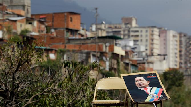 A poster of Venezuela's Hugo Chavez lays against a chair on the top of a home's roof during a rally in Caracas, Venezuela, Wednesday, Jan. 23, 2013. While Venezuela's sick president recuperates from surgery in Cuba, in Venezuela he is alive and well, at least in spirit. (AP Photo/Fernando Llano)