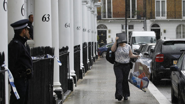 A Police investigation officer, sheltering from the rain with a folder, arrives at the home of Britain's richest women, American-born Eva Rausing who was found dead in her home in Belgravia, London, Wednesday, July 11, 2012. American-born Eva Rausing, was found dead in her west London home and a man was arrested in connection with the case, British police said, adding that an autopsy had failed to uncover a formal cause of death. (AP Photo/Sang Tan)