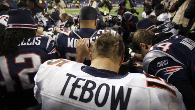 Denver Broncos quarterback Tim Tebow prays with New England Patriots and Broncos team members following an NFL divisional playoff football game Saturday, Jan. 14, 2012, in Foxborough, Mass. The Patriots defeated the Broncos 45-10. (AP Photo/Charles Krupa)