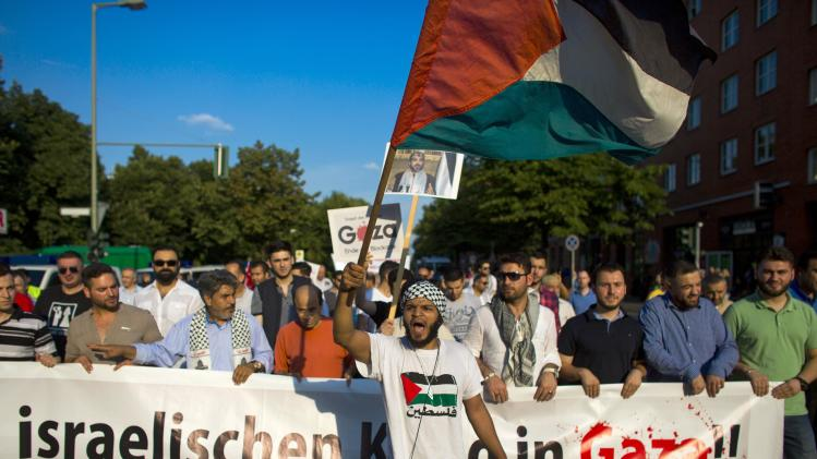 People hold banner during protest in central Berlin denouncing Israeli military actions in Gaza