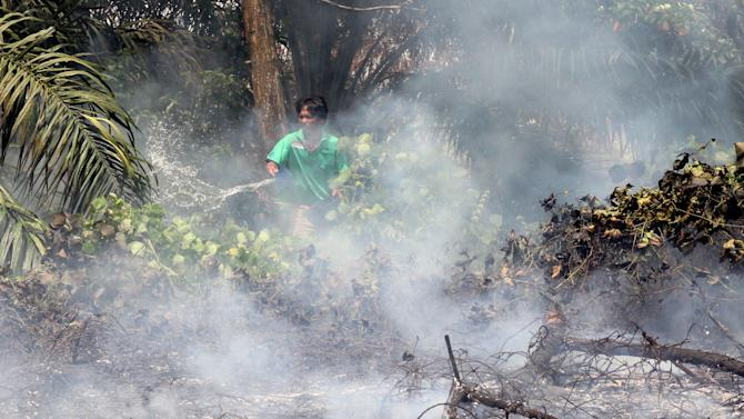 An villager throws a bucket of water on a bushfire in Pekanbaru, Riau province, Indonesia, Friday, June 21, 2013. The blazes in peat swamp forests on Indonesia's Sumatra island have sent massive plumes of smog across the sea to neighboring Singapore and Malaysia, both of which have grown impatient with Indonesia's response to the problem that occurs nearly every year. (AP Photo/Rony Muharrman)