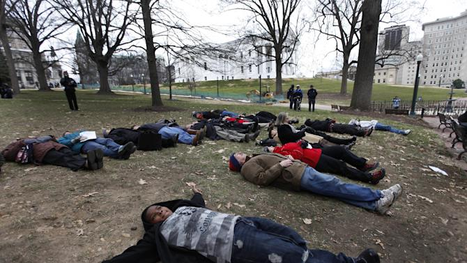 FILE - In a Monday, Jan. 17, 2011 file photo, gun violence protesters participate in a lie-in during an anti-gun rally at the Capitol in Richmond, Va. Nearly six in 10 Americans want stricter gun laws in the aftermath of last month's deadly school shooting in Connecticut, with majorities favoring a nationwide ban on military-style, rapid-fire weapons and limits on gun violence depicted in video games and movies and on TV, according to a new Associated Press-GfK poll. A lopsided 84 percent of adults would like to see the establishment of a federal standard for background checks for people buying guns at gun shows, the poll showed. President Barack Obama was set Wednesday, Jan. 16, 2013 to unveil a wide-ranging package of steps for reducing gun violence expected to include a proposed ban on assault weapons, limits on the capacity of ammunition magazines and universal background checks for gun sales.  (AP Photo/Steve Helber, File)