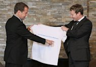 Russian Prime Minister Dmitry Medvedev (left) receives a T-shirt as a present from Facebook CEO Mark Zuckerberg during their meeting at the Gorki residence outside Moscow. Zuckerberg is in Moscow on a visit the government believes should stimulate innovation in Russia and the social network hopes will boost its position in the Russian market