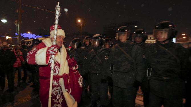 A person dressed up as Ded Moroz (Father Frost)  passes police officers during an unsanctioned rally in downtown  Moscow,  Russia, Monday, Dec. 31, 2012. The Russian opposition protests on the 31st of each month are a nod to the 31st article of the Russian constitution, which guarantees the right of assembly. (AP Photo/Alexander Zemlianichenko)