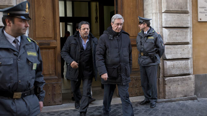 Rev. Franco Decaminada, second right, leaves an Italy's financial police barrack after being questioned in Rome, Thursday, April 4, 2013. Italian police have arrested a Catholic priest accused of pocketing 4 million euros ($5.1 million) from the coffers of a Catholic hospital he ran and helping run up 600 million euros in debts that forced the clinic into bankruptcy and prompted the Vatican to intervene. Italy's financial police placed the Rev. Franco Decaminada, until 2011 the CEO of the IDI dermatological hospital in Rome, under house arrest Thursday and detained two other people while seizing a Tuscan farmhouse police say he purchased with stolen money. (AP Photo/Andrew Medichini)