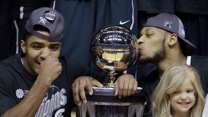 """FILE - In this March 16, 2014 file photo, Michigan State's Gary Harris, left, poses with the championship trophy as Adreian Payne kisses it after they defeated Michigan 69-55 in an NCAA college basketball game in the championship of the Big Ten Conference tournament in Indianapolis. Lacey Holsworth, who is batling cancer, smiles at right foreground. The father of 8-year-old Lacey Holsworth, who befriended Michigan State basketball star Adreian Payne says his daughter has died. Matt Holsworth says Lacey Holsworth died at their St. Johns, Mich., home late Tuesday, April 8, 2014, """"with her mommy and daddy holding her in their arms.""""(AP Photo/Michael Conroy)"""