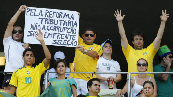 """Fans hold a sign """"Tribute to reform. No corruption. Go ahead Selecao"""" prior to the soccer Confederations Cup group A match between Brazil and Mexico at Castelao stadium in Fortaleza, Brazil, Wednesday, June 19, 2013. (AP Photo/Fernando Llano)"""