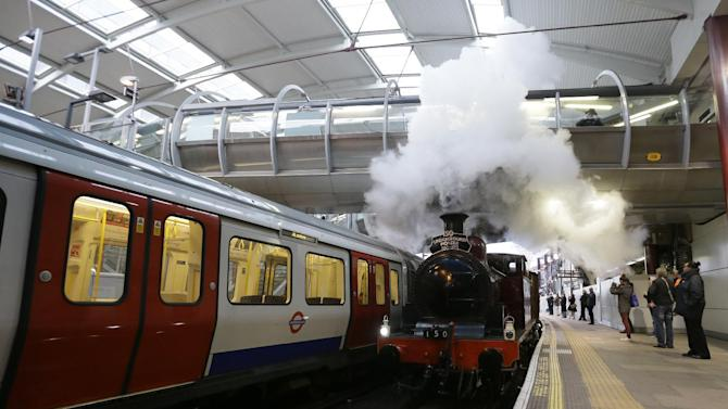 Metropolitan 1, a restored steam train built in 1898, passes a modern tube train through Farringdon Tube station on it's journey between Olympia Tube station in the west to Moorgate station in the City of London, Sunday, Jan. 13, 2013, as part of the celebrations for the 150th anniversary of the London Underground Tube system. The first stretch of the world-famous network opened to the public on Jan. 10, 1863. (AP Photo/Alastair Grant)
