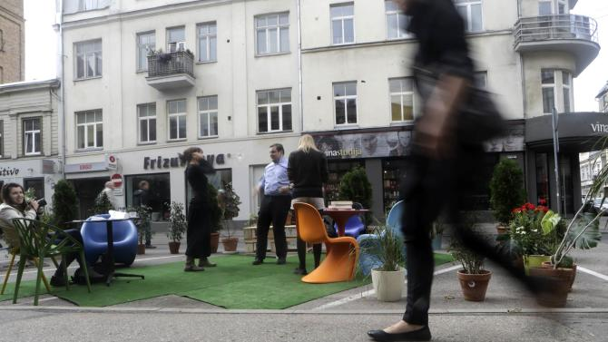 A woman walks past people participating in a PARK(ing) Day event in Riga