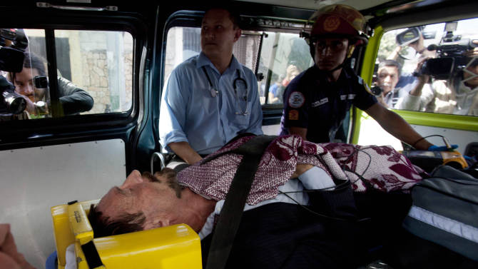 Software company founder John McAfee lies inside an ambulance, to be transferred from an immigration detention center to a hospital, in Guatemala City, Thursday, Dec. 6, 2012 . He was examined by a doctor at the detention center, who said that McAfee's heart and blood pressure were normal, but nonetheless was being moved to a hospital after McAfee was found lying on the floor in the room where he was being detained. McAfee who fled Belize was denied political asylum in Guatemala on Thursday and police in Belize said they expected him to be flown back soon for questioning about the killing of a fellow American expatriate. (AP Photo/Moises Castillo)