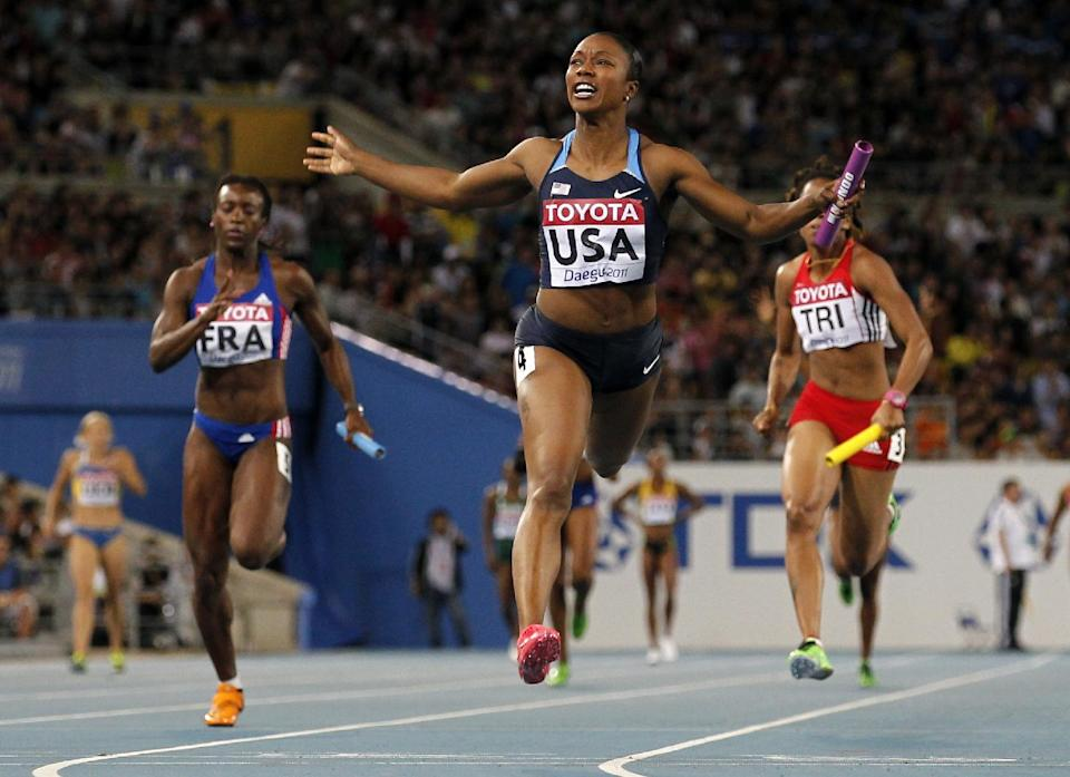USA's Carmelita Jeter, center, crosses the finish line to win the Women's 4x100m Relay final at the World Athletics Championships in Daegu, South Korea, Sunday, Sept. 4, 2011. (AP Photo/Anja Niedringhaus)