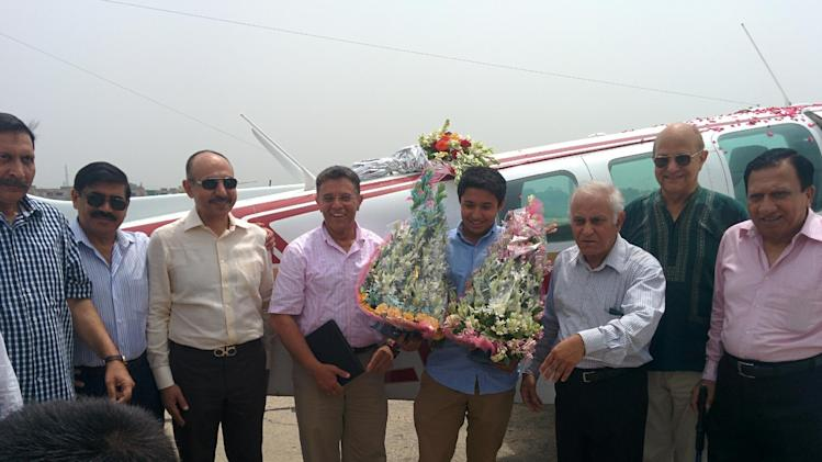 In a photo provided by Citizens Foundation, Haris Suleman, center right, in blue shirt, and his father, Babar Suleman, center left, stand with the plane in early July 2014 in Pakistan that they were flying on an around-the-world trip. Haris Suleman, 17, who was attempting to set a record for an around-the-world flight, was killed when his plane crashed in the Pacific Ocean, and crews were searching Wednesday, July 23, 2014, for his father, who was also on board. Family spokeswoman Annie Hayat said the plane flown by Haris Suleman went down shortly after leaving Pago Pago in American Samoa Tuesday night. Hayat said the body of Haris Suleman had been recovered, but crews were still looking for Babar Suleman. The father and son were using the trip to raise money for the Citizens Foundation, a nonprofit that builds schools in Pakistan. (AP Photo/Citizens Foundation)